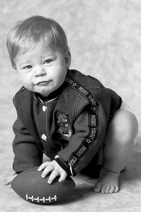 little toddler boy on backdrop crouching with a football, Willa Stein Photography