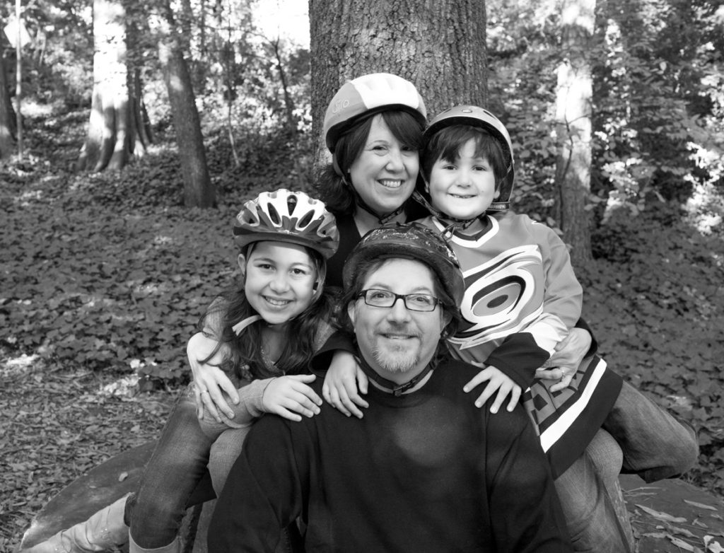 black and white portrait of a family wearing bike helmets, Willa Stein Photography