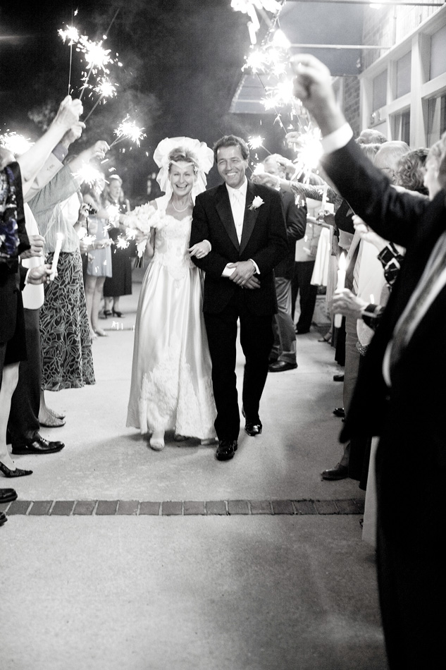 bride and groom walking past chain of folks holding lit sparklers